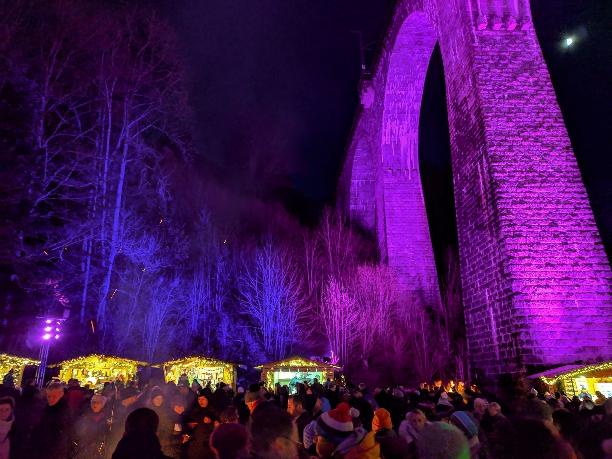 Ravennaschlucht Weihnachtsmarkt, Ravenna Gorge Christmas Markets near Freiburg Germany with a pink illuminated railroad bridge above Christmas stalls.