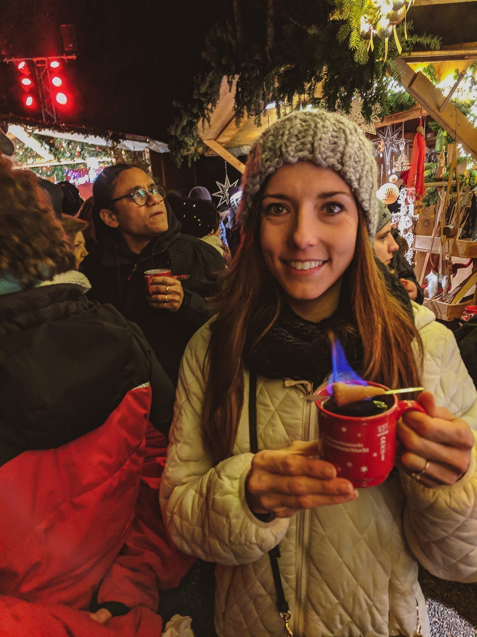 Feuerzangenbowle is a common German Christmas tradition and bought at the famed German Christmas Markets, here is a girl holding a red glass of the flaming Glühwein.